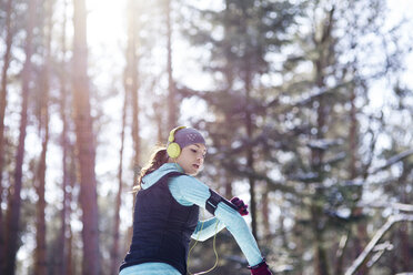 Young woman with headphones jogging in forest - ABIF00296