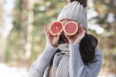 Laughing young woman wearing knitwear covering her eyes with halves of grapefruit - ABIF00299
