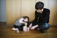 Father looking at daughter playing with toys blocks while sitting on floor - CAVF35398