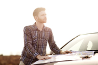 Man with map looking away while standing by car against clear sky - CAVF35416
