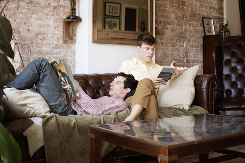 Gay couple reading books while relaxing on sofa at home - CAVF35458