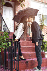 Affectionate lesbian couple kissing while standing on steps against building - CAVF35521