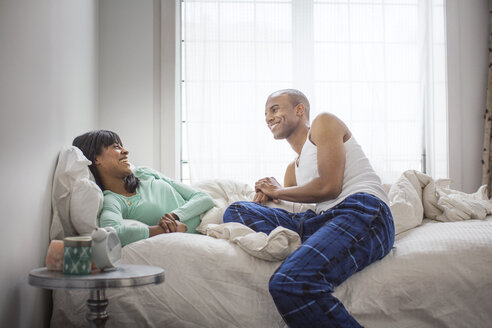 Smiling couple talking while relaxing on bed at home - CAVF35527