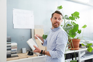 Businessman holding diary working at creative office - MASF01936