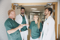 Cheerful medical colleagues talking in hospital corridor - MASF01939