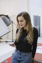 Young woman using smart phone in creative office - MASF01966