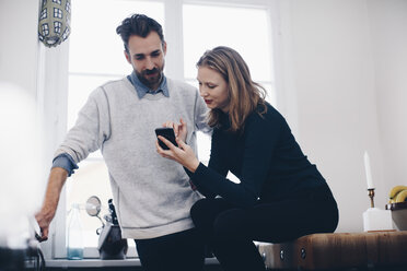 Young woman showing mobile phone to man against window at home - MASF01984