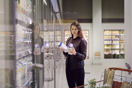 Woman holding juice boxes at refrigerated section in supermarket - MASF01996