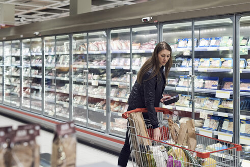 Woman holding container while standing by shopping cart at refrigerated section in supermarket - MASF01999
