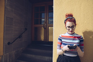 Young female hipster using mobile phone while standing against wall by entrance of building - MASF02002