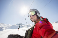 Smiling man in ski-wear on snow covered field against clear sky - MASF02008