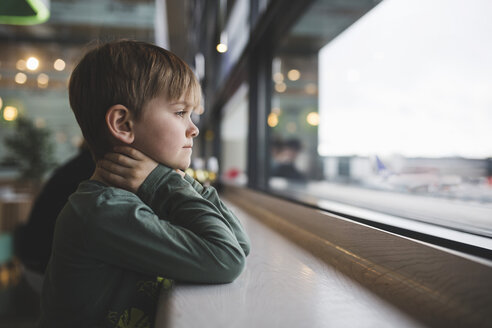Thoughtful boy leaning on table by window of restaurant - MASF02011