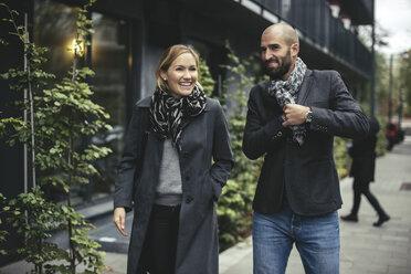 Smiling businessman and businesswoman talking while walking on sidewalk - MASF02029