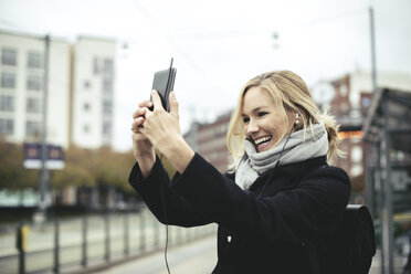Smiling mid adult businesswoman talking selfie through mobile phone at tram station - MASF02032