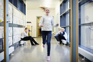 Smiling girl running in school corridor with friends in background - MASF02044
