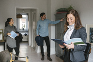 Smiling female real estate agent reading brochure while couple looking at cabinet at home - MASF02050