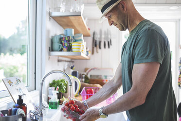 Side view of man washing cherry tomatoes under faucet in kitchen at home - MASF02059