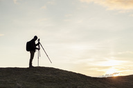 Side view of silhouette hiker fixing tripod on hill against sky during sunset - MASF02065