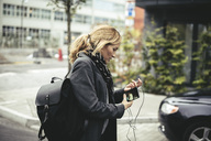 Side view of mid adult businesswoman holding smart phone while walking on city street - MASF02071