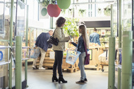 Side view of mother and daughter standing at organic supermarket - MASF02077