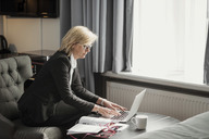 Side view of businesswoman using laptop by window at hotel room - MASF02083