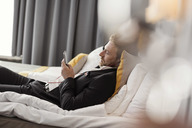 Side view of businessman listening music while lying on bed at hotel room - MASF02086