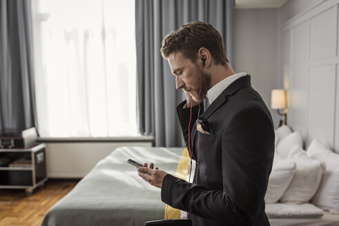 Side view of businessman listening to mobile phone in hotel room - MASF02089