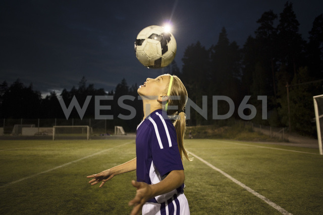 Side view of girl heading the ball on field against sky - MASF02092 - Maskot ./Westend61