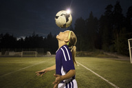Side view of girl heading the ball on field against sky - MASF02092