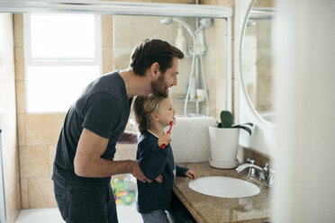 Side view of father watching daughter brushing teeth at sink in bathroom - MASF02101