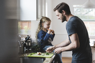 Side view of father cooking food while daughter having apple in kitchen - MASF02104