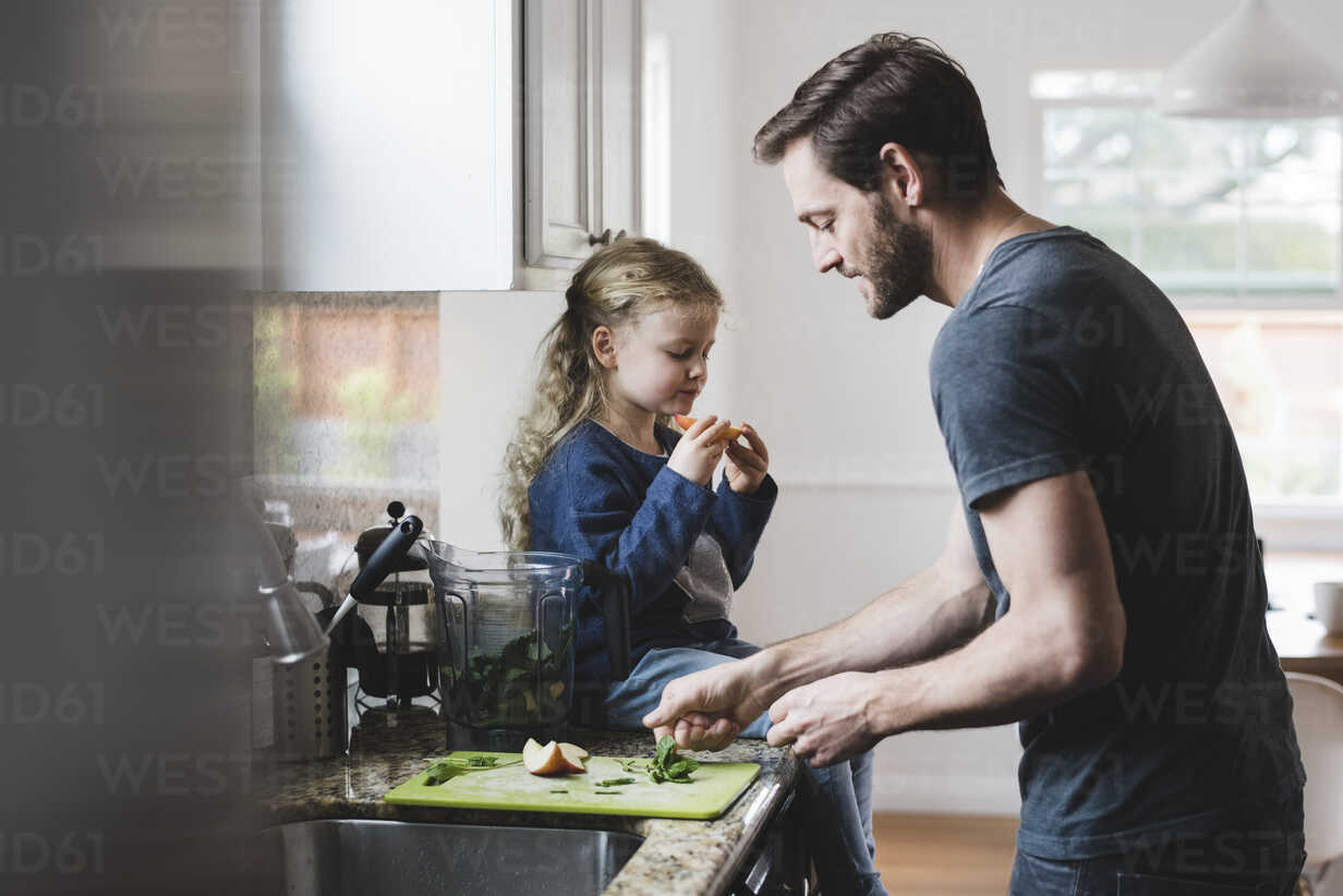 Side view of father cooking food while daughter having apple in kitchen - MASF02104 - Maskot ./Westend61
