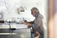 Side view of senior man using digital tablet while doing paperwork seen through glass - MASF02107