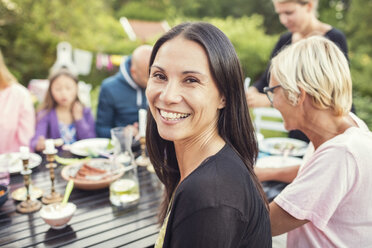 Portrait of happy woman sitting with family and friends at dining table in back yard during garden party - MASF02114