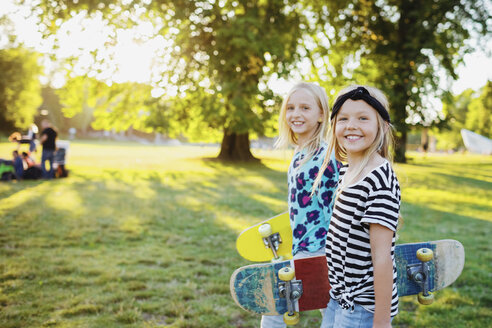 Portrait of smiling friends with skateboards at public park - MASF02120