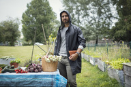 Portrait of mid adult man standing by freshly harvested vegetables on table at urban garden - MASF02129