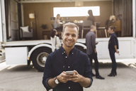 Portrait of smiling businessman holding mobile phone with colleagues and portable office truck on road in background - MASF02138
