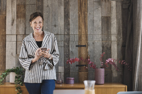 Portrait of happy businesswoman holding smart phone against wood paneling in portable office truck - MASF02141