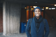 Portrait of happy man wearing blue warm clothing and knit hat standing in campus - MASF02144