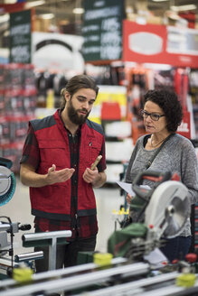 Salesman explaining power tools to mature woman in hardware store - MASF02171