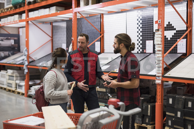 Salesman discussing with couple by shelves at hardware store - MASF02174