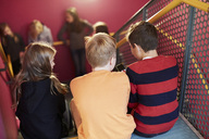 Rear view of junior high students sitting on staircase - MASF02177