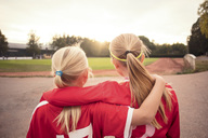 Rear view of female soccer friends standing on footpath looking at field during sunset - MASF02183