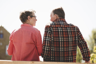 Rear view of senior couple looking at each other while standing against clear sky - MASF02195