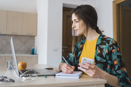 Young woman sitting at table at home using cell phone and laptop taking notes - KKAF00914