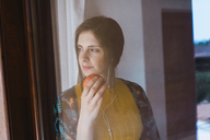 Young woman with earphones and apple looking out of window - KKAF00923
