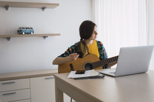 Young woman sitting at table at home with laptop playing guitar - KKAF00926