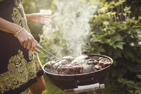 Midsection of woman grilling meat on barbecue in back yard - MASF02200