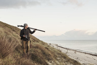 Photographer looking away while carrying tripod on hill by sea - MASF02215