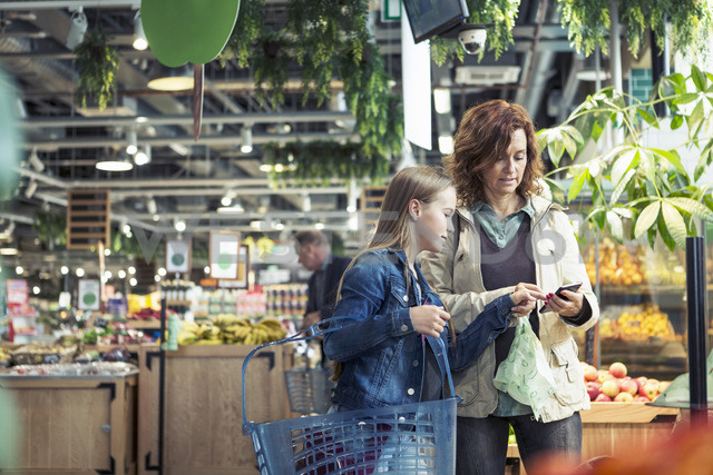 Mother and daughter using smart phone in organic foodstore - MASF02221